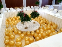Złote balony z powietrzem jako dekoracja części bankietowej sali.