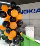 Balony na patyczkach ułożone na stojaku.