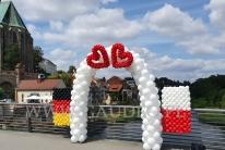 Brama z balonów z flagami Polski i Niemiec.