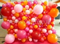 Balony o różnych wielkościach ułożone w formie ściany.