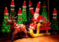 Balonowe choinki i Mikołaj w saniach ciągniętych przez renifera.