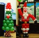 Balonowy Mikołaj razem z choinką w mikołajowej czapce.