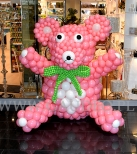 Balonowy misio jako dekoracja salonu z odzieżą dziecięcą.