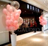 Balony z helem i konfetti w donicach jako dekoracja z okazji otwarcia nowego sklepu.