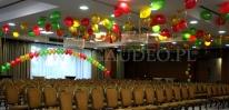 Balony z helem pod sufitem wykorzystane do dekoracji sali na imprezie.