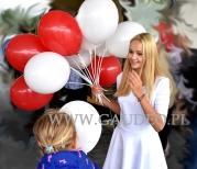 Biało-czerwone balony patriotyczne rozdawane przez hostessę.