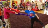 Chłopcy bawią się szablami skręconymi z balonów.