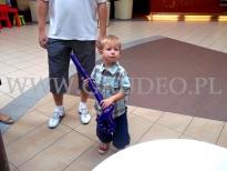 Chłopiec z balonową szablą przy stoisku promocyjnym firmy.