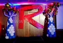 """Duża litera """"R"""" wykonana z balonów jako dekoracja sceny na konferencji firmowej."""