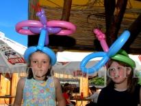 Dziewczynki w balonowych stroikach na głowach na pikniku.