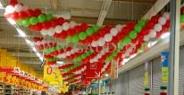 Girlandy balonowe nad kasami w hipermarkecie Auchan.
