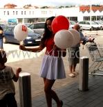 Przed sklepem hostessa rozdaje balony z nadrukiem na patyczkach.