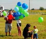 Hostessa rozdaje balony z helem na pikniku.
