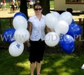 Hostessa rozdaje balony z nadrukiem w czasie pikniku firmowego.
