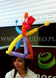 Hostessa w stroiku z balonów na głowie.
