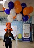 Hostessa w kapeluszu z balonów rozdaje balony reklamowe.