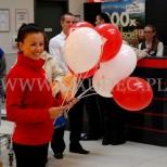 Śliczna hostessa z balonami reklamowymi na patyczkach.