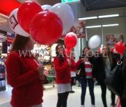 Hostessy rozdają balony na patyczkach.