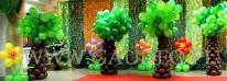 Impreza dla dzieci udekorowana balonowymi drzewami i kwiatami.