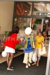 Hostessa wręcza balony reklamowe z nadrukiem wychodzącym klientkom sklepu.