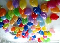 Balony z helem w kolorach tęczy unoszą się pod sufitem firmy.