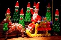 Mikołaj z balonów pędzi rozdawać prezenty.
