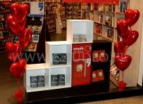 Walentynkowa dekoracja wystawy sklepowej balonowymi serduszkami z helem.